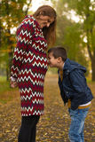 Mom and son in park. Small boy kissing belly of his pregnant mother outdoors stock photos