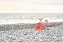 Mom and son play on the beach. Back view royalty free stock photo