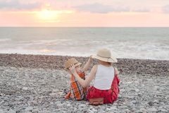 Mom and son play on the pebble beach. Sunset time. Back view royalty free stock photography