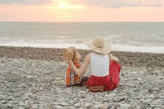 Mom and son play on the pebble beach. Sunset time. Back view royalty free stock photos