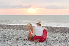 Mom and son play on the pebble beach. Sunset time. Back view stock photos