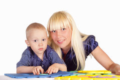 Mom and son playing. Cute mom and her son playing at table Royalty Free Stock Images