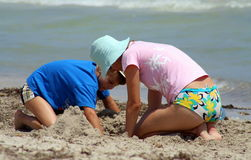 Mom and son playing on beach. Young mother and son building sand castles on beach with sea in background Royalty Free Stock Image