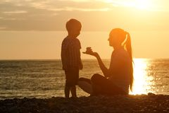 Mom and son playing on the beach with stones. Sunset time, silhouettes.  Royalty Free Stock Photos