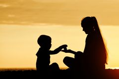 Mom and son playing on the beach with stones. Sunset time, silhouettes.  Royalty Free Stock Images