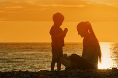 Mom and son playing on the beach with stones. Sunset time, silho. Uettes Royalty Free Stock Photos