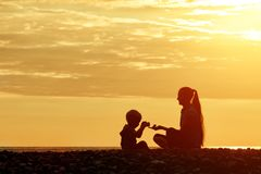 Mom and son playing on the beach with stones. Sunset time, silho. Uettes Royalty Free Stock Photo