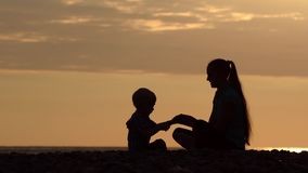 Mom and son playing on the beach with stones. Sunset time, silhouettes.  stock video footage