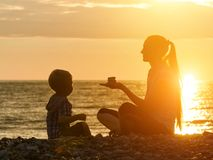 Mom and son are playing on the beach at sunset.  Stock Photos