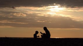 Mom and son playing on the beach. Sunset time, silhouettes.  stock footage