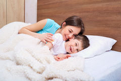 Mom and son playing on the bed. Happy family Stock Images