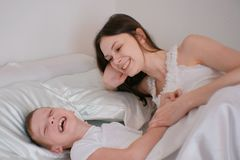 Mom and son playing with each other lying in bed in the morning. stock images