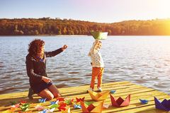 Mom and son playing with paper boats by the lake. Warm filter and film effect Royalty Free Stock Image