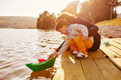 Mom and son playing with paper boats by the lake. Warm filter and film effect Stock Image