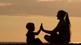 Mom and son playing play in the hands on beach. Sunset time, silhouettes.  stock footage