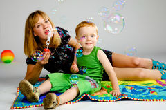 Mom and son playing with soap bubbles. White background studio Stock Image
