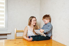 Mom and son playing with a tablet in the kitchen Royalty Free Stock Photography