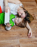 Mom and son playing with tablet pc while lying on the floor Royalty Free Stock Image