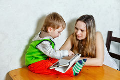 Mom and son playing with tablet PC. Young mother and son playing with the tablet. Sitting in the kitchen. Happy family. Child holding a tablet PC. Happy Stock Images