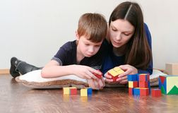 Mom and son playing together wooden colored education toy blocks lying on the floor. Mom and son playing together wooden colored education toy blocks lying on stock photography