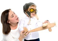 Mom and son are playing with a toy airplane. Mom and son are playing with a toy wooden plane. The concept of a happy childhood, raising a child in the family Stock Image