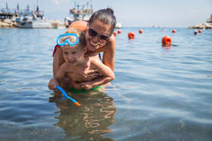 Mom and son playing in the water. A lovely summer day. Leisure at sea. The joy of gaming Royalty Free Stock Photos