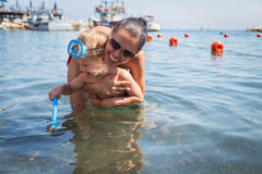 Mom and son playing in the water. A lovely summer day. Leisure at sea. The joy of gaming Stock Photos