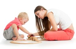 Mom and son are playing wooden railway with train, wagons and tunnel sitting on the floor royalty free stock photo