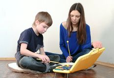 Mom and son playing xylophone sitting in a room on the floor. Mom and son playing xylophone sitting in a room on the floor Stock Photography