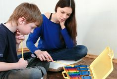 Mom and son playing xylophone sitting in a room on the floor. Mom and son playing xylophone sitting in a room on the floor Stock Image
