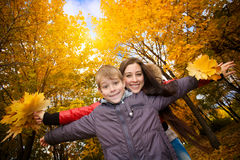 Mom and son are playing in a yellow autumn park Royalty Free Stock Photos