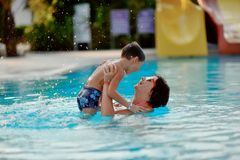 Mom and son in the pool. Mom and son having fun in the summer playing in the pool Royalty Free Stock Image