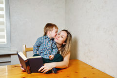 Mom and son reading a book. Mother and son reading a book. Mother holding a book hugging son. Boy kisses his mother. Happy family leisure Stock Photos