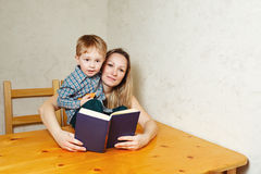 Mom and son reading a book. Mother and son reading a book. Mother holding a book hugging son sitting on the kitchen table. Happy family leisure Royalty Free Stock Photo