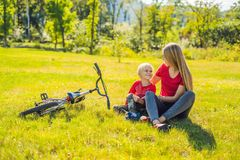 Mom and son rest on the lawn after riding a bike royalty free stock photo