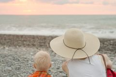 Mom and son rest on the pebble beach. Sunset time. Back view royalty free stock photography