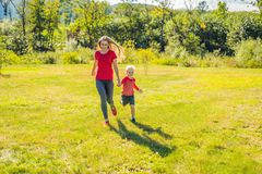 Mom and son run on the green grass. Happy family in the park stock photos
