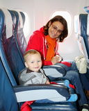 Mom and son sit inside an aircraft and ready to take off Royalty Free Stock Images