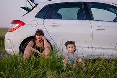 Mom and Son Sits Beside the Car While Waiting Royalty Free Stock Photos