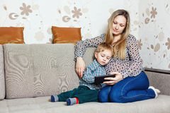 Mom and son sitting on the couch with a tablet PC royalty free stock photos