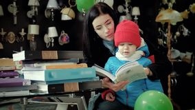 Mom and son flipping through the catalog choose goods in the store. Mom and son are sitting at a table on which there are many different magazines, leafing stock footage