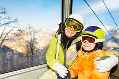 Mom and son skiers sit in cable car ski lift Stock Images