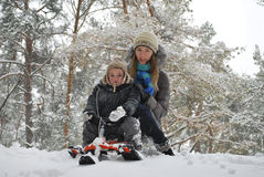 Mom and son sledding in the winter with snow-covered forest, fro Royalty Free Stock Photos