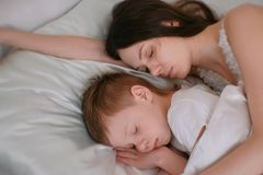 Mom and son sleeping together. Mom hugging her son. royalty free stock image