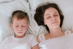 Mom and son sleeping together. Top view. royalty free stock image