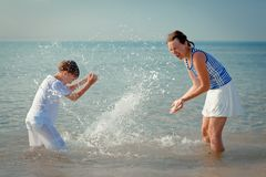 Mom and son splashing water at sea Stock Images