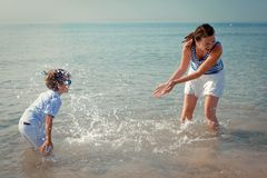 Mom and son splashing water at sea Stock Photo