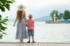 Mom and son standing on the pier on the sea background, lighthouse and mountains in the distance. Back view Royalty Free Stock Photos