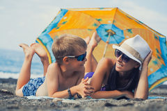 Mom and son are sunbathing on a beach Stock Image