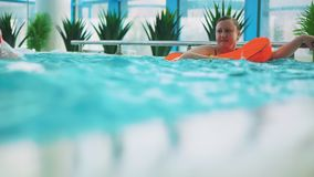 Mom and son swim in the pool. They are in a public aqua park stock video